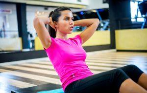 daniele macri personal trainer roma allena donna in palestra esercizio addominali alti